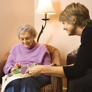 Home care worker providing comfort to an elderly lady