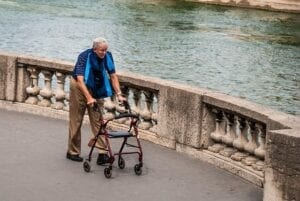 Older man getting physical exercise by walking despite looking frail.