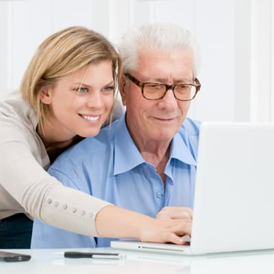 Carer helps man with laptop