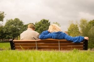 Elderly man and care worker sitting outdoors in a nature park
