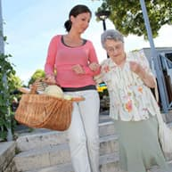 Home carer and elderly lady walking back from shops